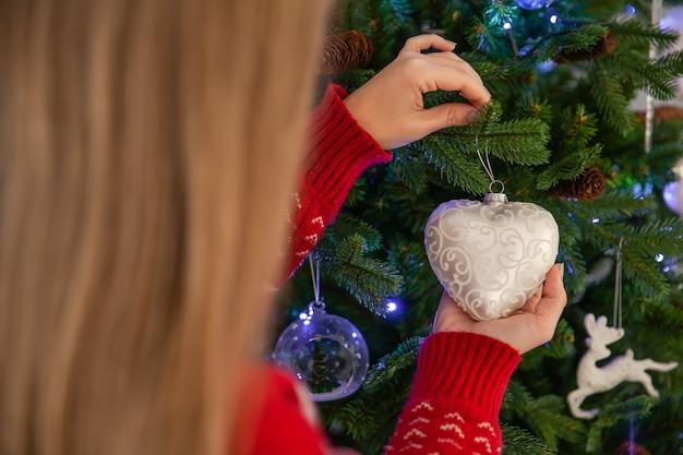 Ciérrese para arriba de la mujer feliz que adorna el árbol de navidad, concepto de días de fiesta de año nuevo