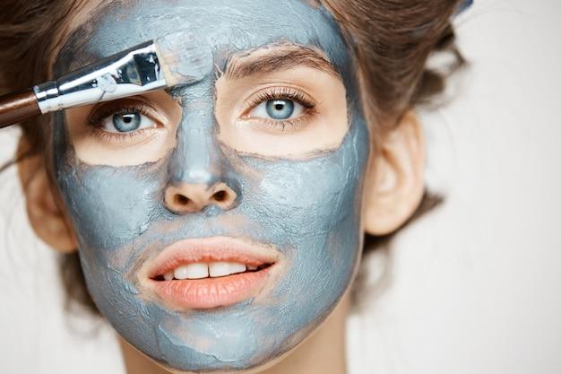 Ciérrese para arriba de mujer hermosa en bigudíes de pelo que sonríe cubriendo la cara con mack. tratamiento facial. cosmetología de belleza y spa.