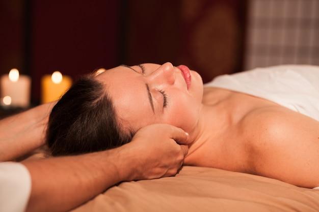 Ciérrese para arriba de la mujer hermosa joven que miente en su parte posterior, recibiendo el masaje relajante del cuello en el salón de belleza. terapeuta profesional de spa masajeando el cuello de su cliente. mujer atractiva que tiene masaje relajante