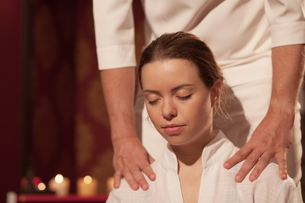 Ciérrese para arriba de una mujer hermosa que disfruta del masaje tailandés profesional con los ojos cerrados en el centro del balneario. mujer relajante mientras masajista realiza masaje tailandés tradicional. salud, mimar