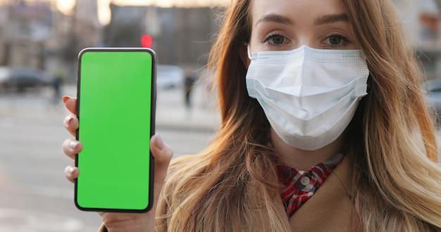 Ciérrese para arriba de mujer joven caucásica en la máscara médica que muestra el teléfono vertical con la pantalla verde. chica con protección antivirus demostrando smartphone con clave de croma verticalmente en la ciudad.