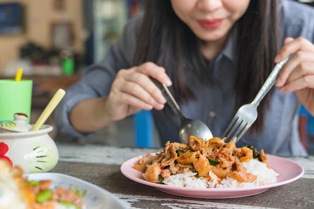 Ciérrese para arriba de la mujer joven que come la comida tailandesa en restaurante