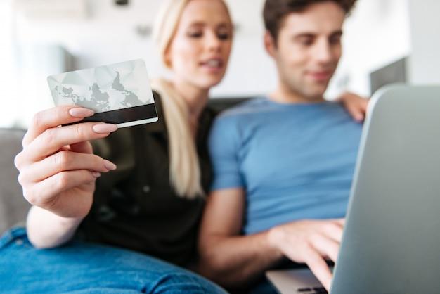 Ciérrese para arriba de la mujer joven que sostiene la tarjeta de crédito mientras que usa la computadora portátil con su marido