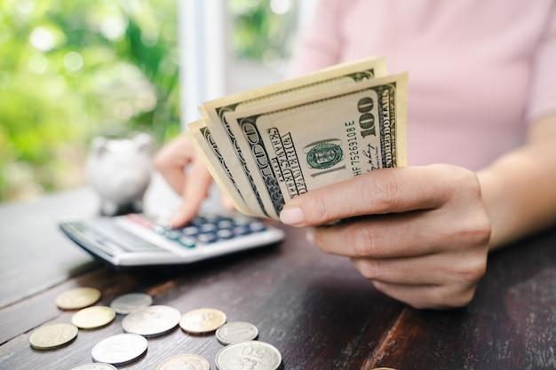 Ciérrese para arriba de mujer de negocios con la calculadora que cuenta el dinero. ahorro de dinero y concepto financiero