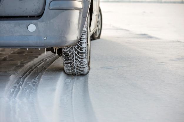 Ciérrese para arriba de un neumático de coche estacionado en el camino nevoso el día de invierno. concepto de transporte y seguridad.
