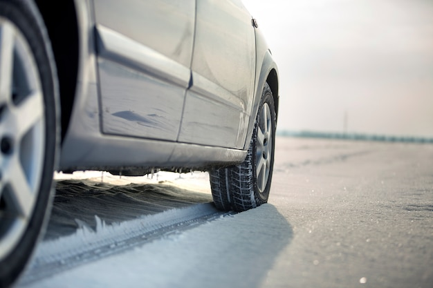 Ciérrese para arriba de un neumático de coche estacionado en el camino nevoso el día de invierno. transporte y seguridad.