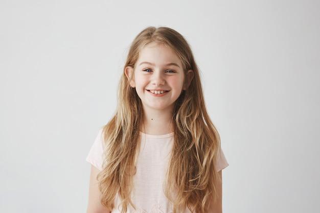 Ciérrese para arriba de niña divertida con los ojos azules y el pelo rubio que ríen, con la expresión satisfecha, posando para la foto de familia.