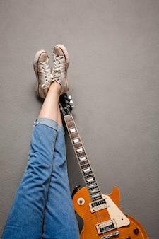 Ciérrese para arriba de las piernas y de la guitarra de la muchacha sobre fondo gris.