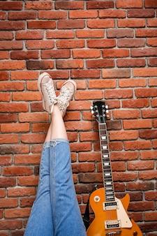 Ciérrese para arriba de las piernas y de la guitarra de la muchacha sobre fondo del ladrillo.