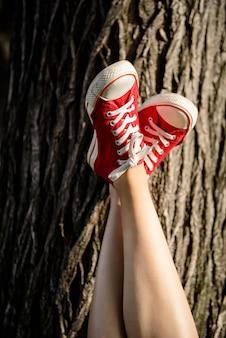 Ciérrese para arriba de las piernas en los keds rojos que mienten en la madera.