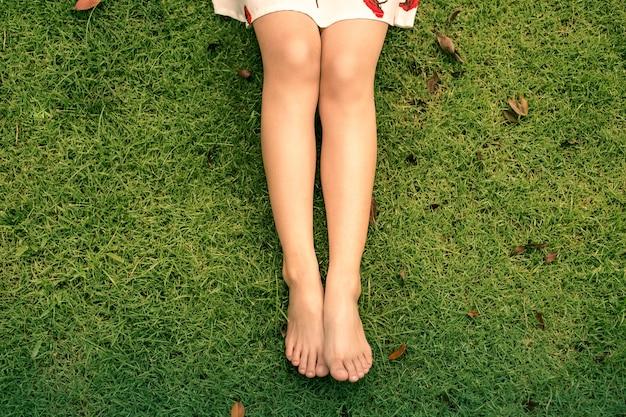 Ciérrese para arriba de las piernas de una mujer que mienten en la hierba en un parque en un día soleado