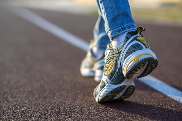 Ciérrese para arriba de pies de la mujer en zapatillas de deporte y tejanos en carril para correr en cancha de deportes al aire libre.