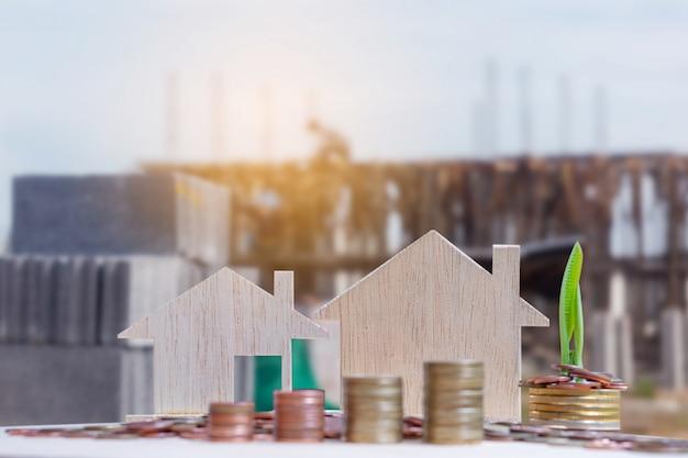 Ciérrese para arriba de la pila del modelo de la casa y de la moneda del dinero con el fondo borroso del sitio de construcción