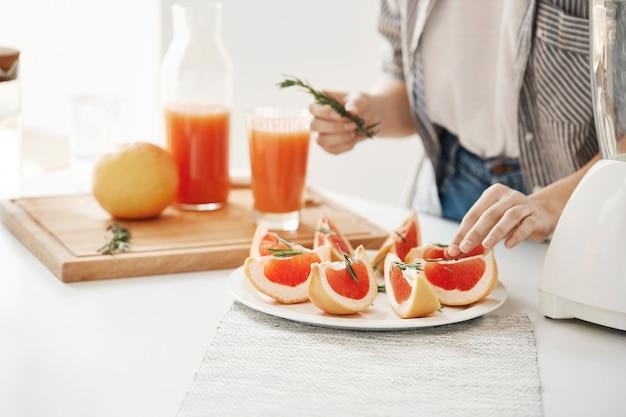Ciérrese para arriba de la placa de decoración de la muchacha con el pomelo y el romero rebanados. concepto de nutrición fitness. copia espacio