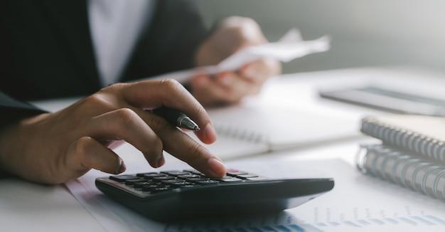 Ciérrese para arriba de la pluma de tenencia de la mano del hombre de negocios o del contador que trabaja en la calculadora para calcular los datos comerciales, concepto de la contabilidad financiera