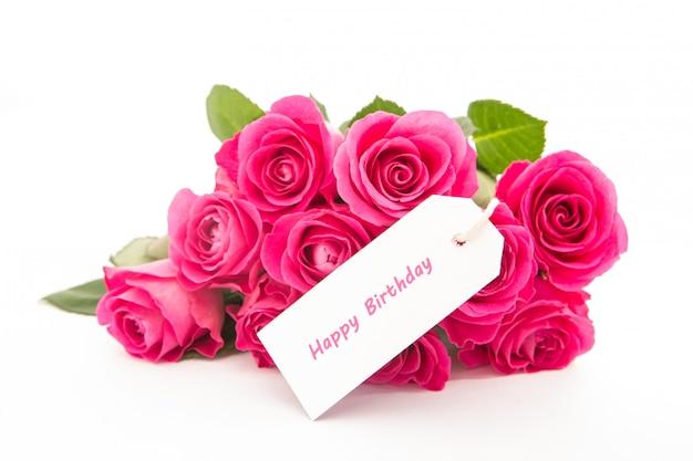 Ciérrese para arriba de un ramo hermoso de rosas rosadas con una tarjeta del feliz cumpleaños en un fondo blanco