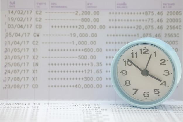 Ciérrese para arriba del reloj redondo del vintage en la libreta de banco del banco de cuenta bancaria.