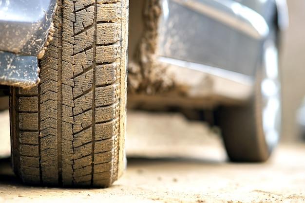 Ciérrese para arriba de la rueda de coche sucia con el neumático de goma cubierto con fango amarillo.