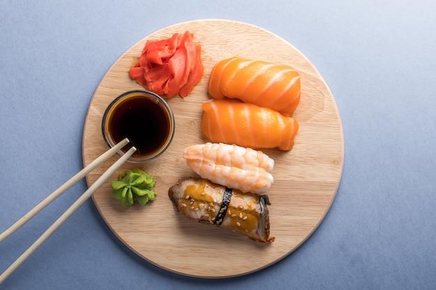 Ciérrese para arriba del sistema del sushi del sashimi servido en la placa de madera. sabrosos mariscos japoneses, concepto de restaurante