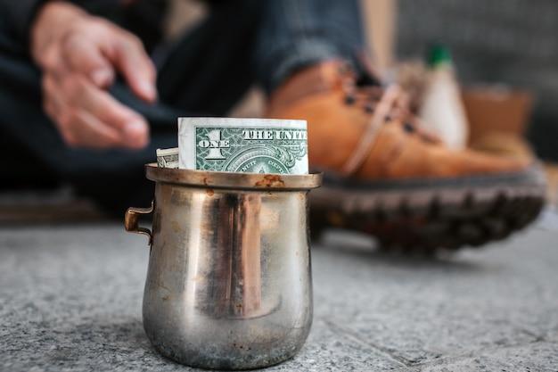 Ciérrese para arriba de la taza vieja del metal que se coloca en el asfalto