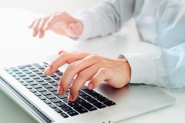 Ciérrese para arriba del teclado que mecanografía del hombre de negocios con el ordenador portátil en el escritorio blanco en oficina moderna