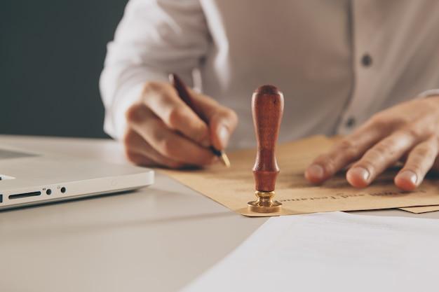 Ciérrese para arriba en tinta de la mano del notario público del hombre que sella el documento. concepto de notario público
