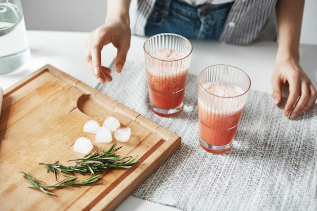 Ciérrese para arriba de los vidrios de las manos de la mujer con los pedazos del romero y del hielo del smoothie de la dieta de la desintoxicación del pomelo en el escritorio de madera.