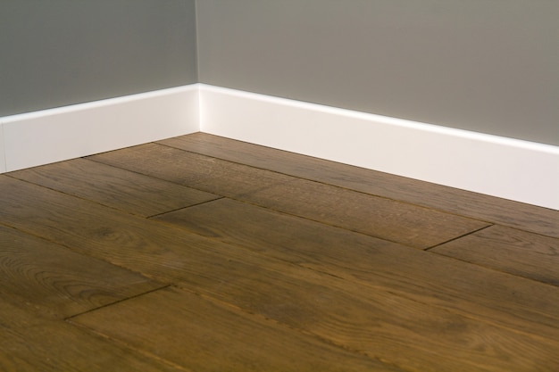 Ciérrese para arriba de los zócalos plásticos blancos en el entarimado de madera oscuro del piso de roble.