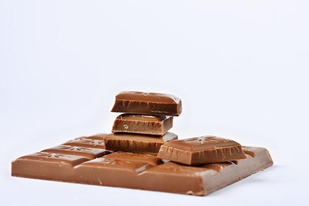 Ciérrese encima de una barra de chocolate aislada en el fondo blanco.