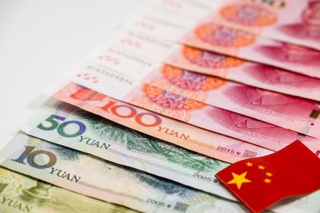 Ciérrese encima de los billetes de banco de china yuan y de la bandera de china en el fondo blanco concepto de la economía.