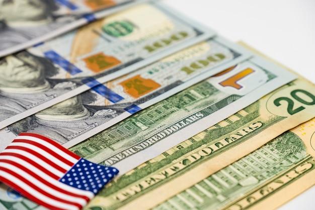 Ciérrese encima de los billetes de banco del dólar de los eeuu y de la bandera de los estados unidos de américa en el fondo blanco.