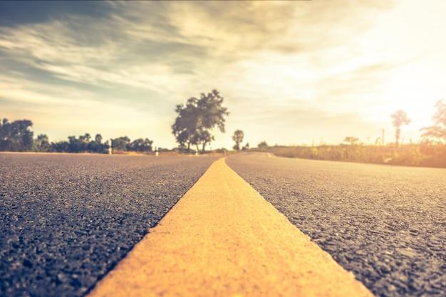 Ciérrese encima de la carretera de asfalto, carretera de carreteras en escena rural vintage hipster viaje por carretera paisaje.