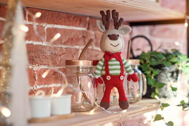 Ciérrese encima de los ciervos del amigurumi del juguete en suéter rayado y el lazo elegante de la mariposa roja se coloca en el estante de madera cerca del árbol de navidad y de las luces de navidad adornados.