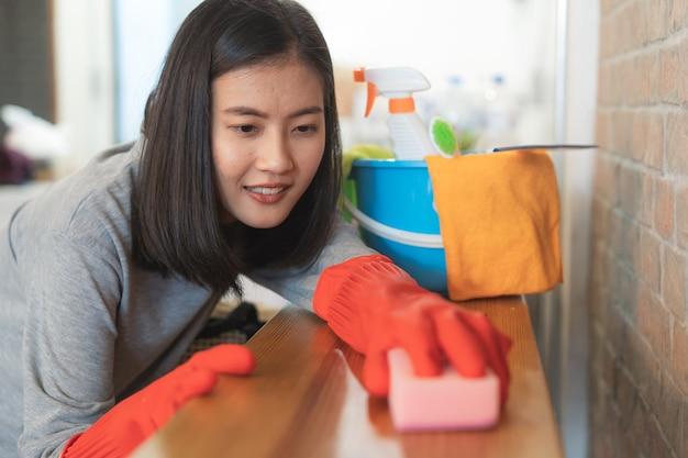 Ciérrese encima de la cocina de la limpieza de la mujer usando el aerosol y el paño de la despedregadora.