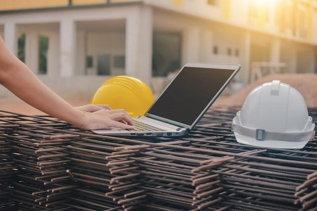 Ciérrese encima de la computadora del teclado de mecanografía de la mano en el sitio de la construcción del trabajo de la construcción