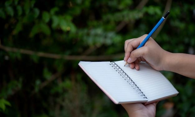 Ciérrese encima del cuaderno de la escritura de la pluma de tenencia de la mano en el fondo de madera