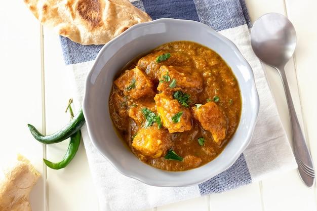 Ciérrese encima del curry indio tradicional del pollo de la mantequilla servido con pan del chapati en cuenco. vista superior.