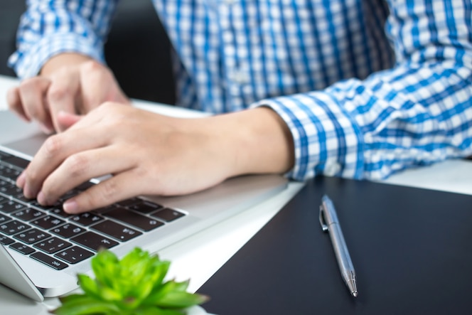 Ciérrese encima de las manos de un hombre que lleva una camisa azul de la tela escocesa que mecanografía en la computadora portátil del teclado.