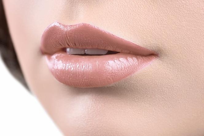 Ciérrese encima de tiro de los labios de una mujer que lleva lápiz labial o labio glo
