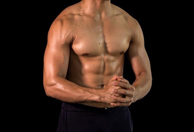 Ciérrese encima del cuerpo hermoso muscular del culturista en fondo negro