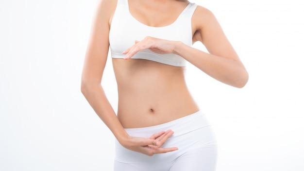 Ciérrese encima de dieta hermosa del cuerpo de la mujer con las manos alrededor de su estómago.