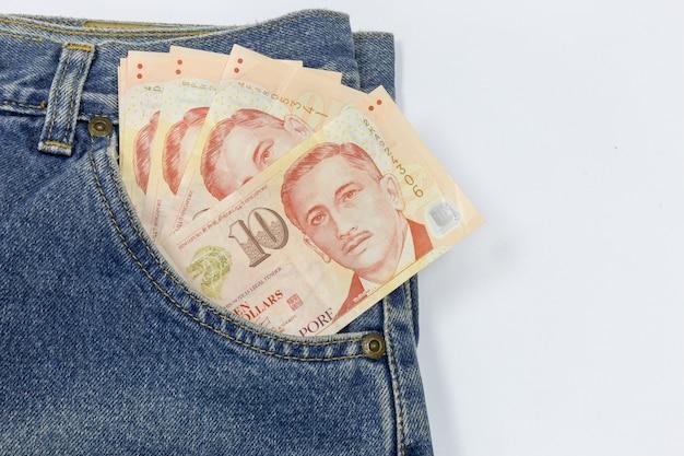 Ciérrese encima de los dólares de singapur en un bolsillo de los pantalones vaqueros en el fondo blanco