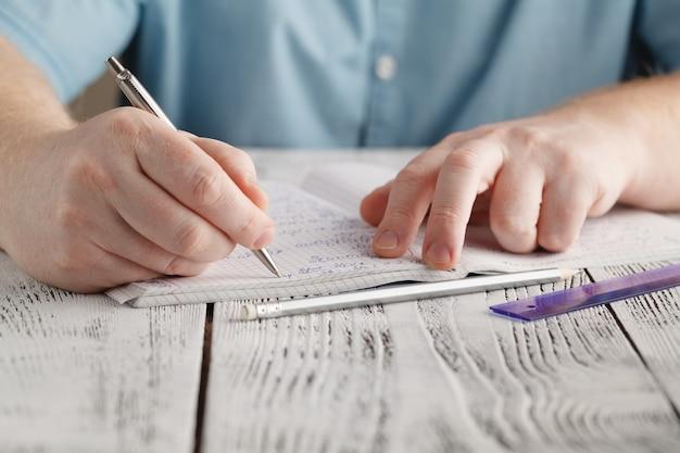 Ciérrese encima de la escritura de la mano del varón en el papel, escribiendo las matemáticas desordenadas, estudiante que sostiene la pluma que hace la tarea en casa, calcula los resultados en el papel, concepto de la educación