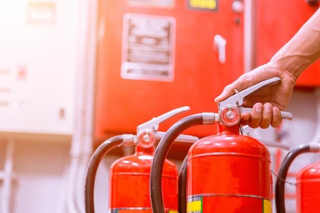 Ciérrese encima del extintor y del perno de tracción en el tanque rojo.
