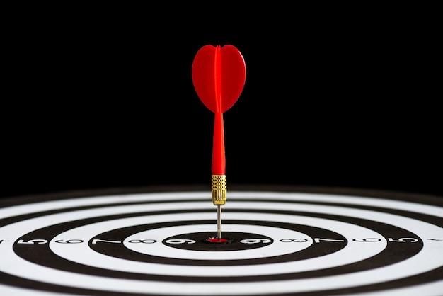 Ciérrese encima de flechas rojas de los dardos del tiro en el centro de la blanco en fondo negro.