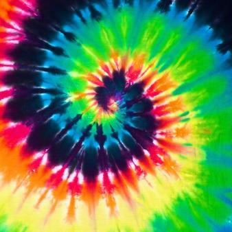 Ciérrese encima de fondo colorido de la textura de la tela del teñido anudado