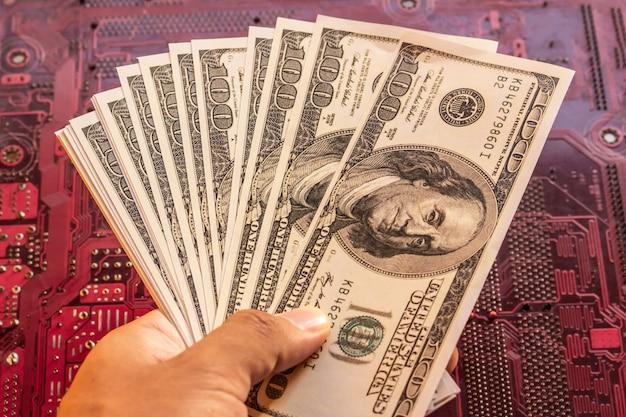 Ciérrese encima de fondo del hombre y de la placa de circuito del dólar a mano.