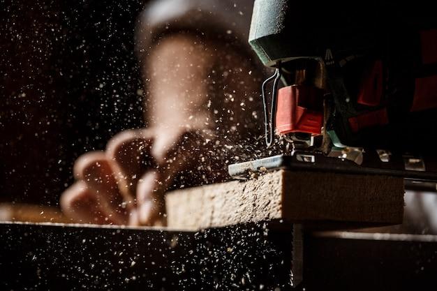 Ciérrese encima de la foto de cortar la madera con la segueta.