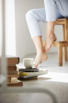 Ciérrese encima de la foto de libros y de la taza de café que miente en piso. piernas de mujer en silla.