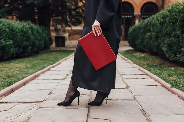 Ciérrese encima de la foto de la mujer en la capa que sostiene el certificado cerca de universidad.